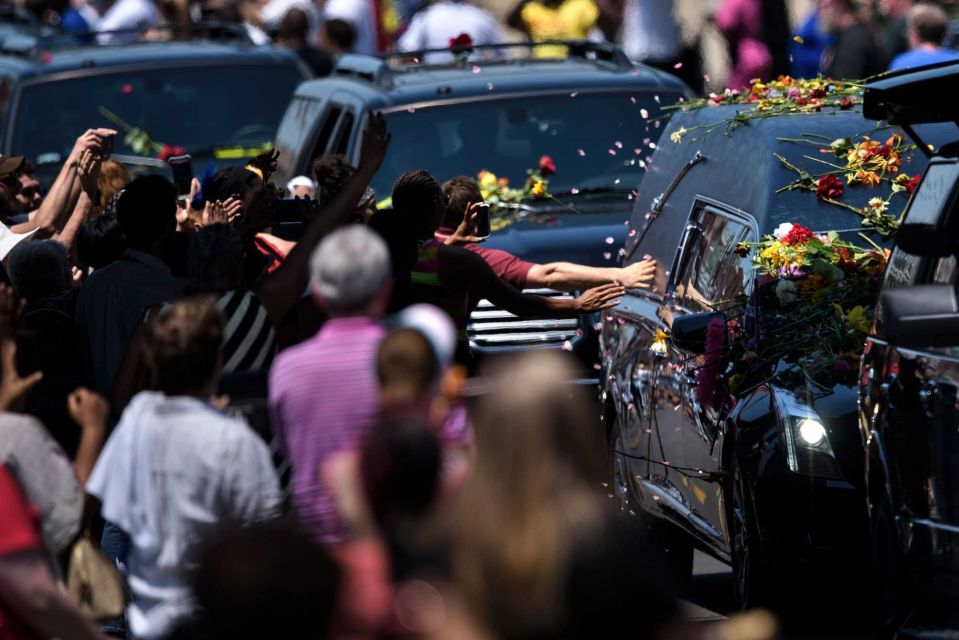 People reach out to touch a hearse with