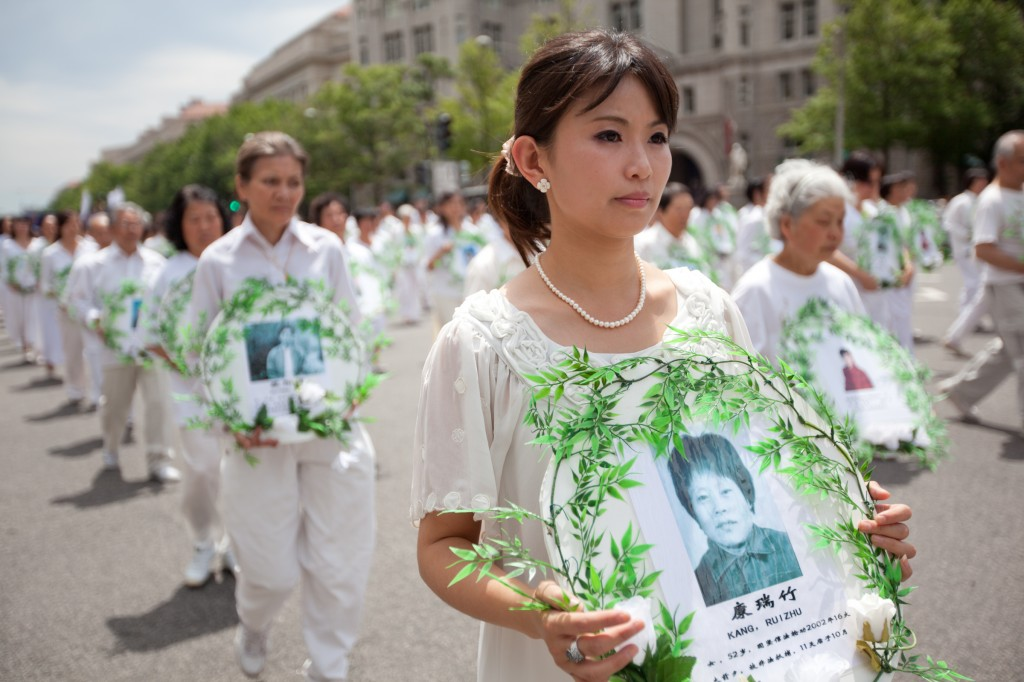 Marching Falun Gong practitioners hold photos of victims of the persecution during a parade in Washington, on July 18, 2011. (Epoch Times)