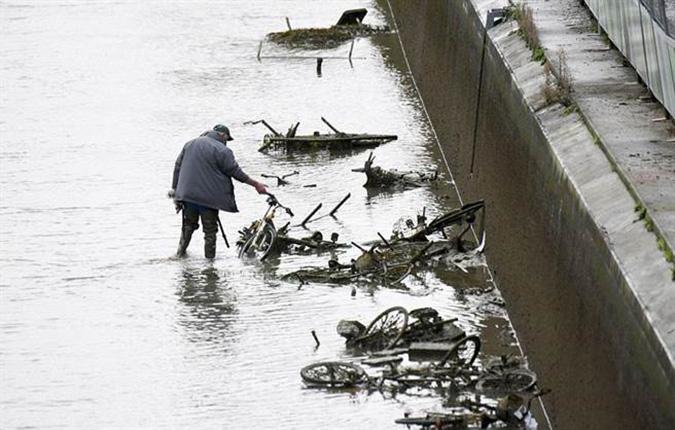 Một người đàn ông đến nhìn các chiếc xe đạp đươc thải ra dưới kênh đào. (Ảnh: Online International)