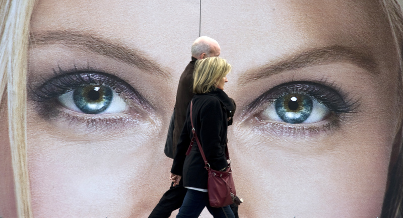 A couple walks past an advertising billboard for cosmetics, featuring a close-up of a pair of women's eyes, in Berlin on May 4, 2011. AFP PHOTO / JOHN MACDOUGALL (Photo credit should read JOHN MACDOUGALL/AFP/Getty Images)