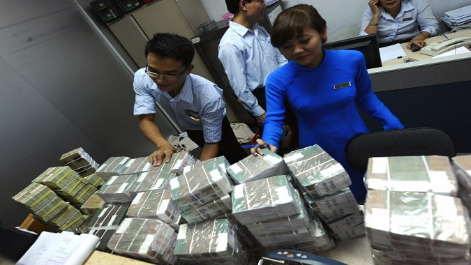 Employees of a local Asia Commercial Bank (ACB) outlet arrange bricks of dong bank notes sent in from the state bank in Hanoi on August 23, 2012. Vietnamese stocks fell for a second day on August 22 as nervous investors struggled to understand the implications of the arrest of a top banking tycoon on suspicion of illegal business activities. AFP PHOTO / HOANG DINH Nam / AFP PHOTO / HOANG DINH NAM
