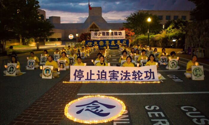 "Falun Gong practitioners hold a candlelight vigil outside the Chinese Embassy in Washington on July 17, 2020. The Chinese character in the foreground is ""memorial."" The sign held by those in the front row says, ""Stop the Persecution of Falun Gong."" (Lisa Fan/The Epoch Times)"