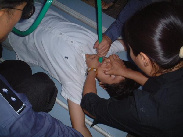 Policemen use a force-feeding torture method on a Falun Gong practitioner at the Hongqiao District Detention Center in Tianjin, China, in this file photo. (Courtesy of Minghui.org)